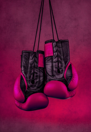 pink boxing gloves hanging on the wall, close-up. motivation in sport.