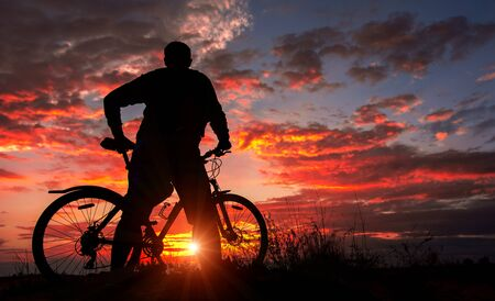 cyclist on the mountain with a bicycle, admiring the fiery sunset.