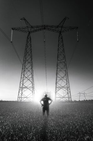 guy on the background of high-voltage power lines at sunset. green field. distribution station. high voltage electric transmission tower.