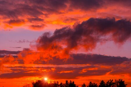 Fiery orange sunset colorful and speckled  clouds. Beautiful sky. Stockfoto
