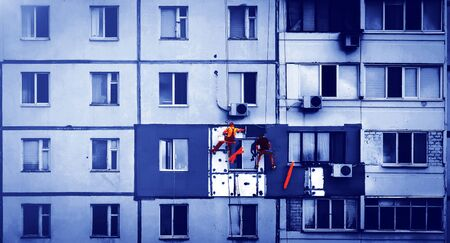 construction work at height. Working high-rise workers mount a house facade.