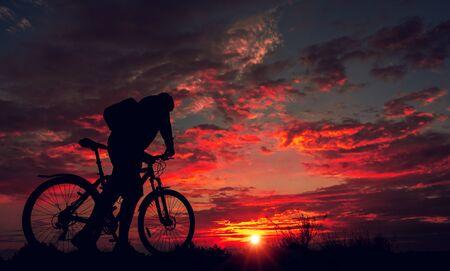 Radfahrer auf dem Berg mit dem Fahrrad und bewundern den feurigen Sonnenuntergang.