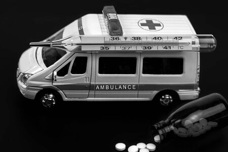 ambulance car with thermometer and pills on blured background. Ambulance auto paramedic emergency.