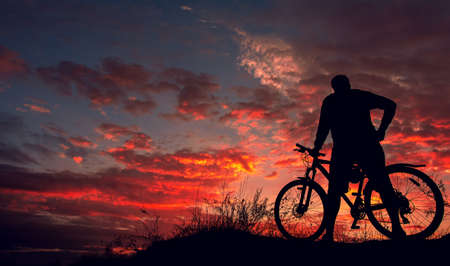 cyclist on the mountain with a bicycle, admiring the fiery sunset. Foto de archivo - 150903561