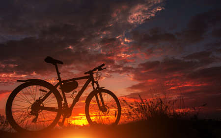 bike silhouette on the mountain, in the background fire sunset. 免版税图像