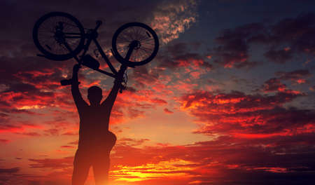 tourist with a bicycle on the background of a fantastic fiery sunset. cyclist silhouette.
