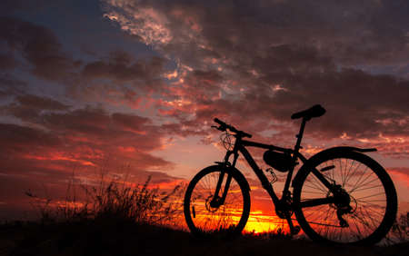 bike silhouette on the mountain, in the background fire sunset. Stock Photo