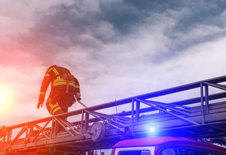 fireman extinguishes the fire at sunset with fire engine. Stock Photo