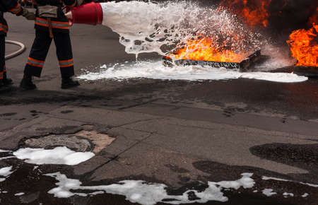 fireman extinguishes the fire with smoke. Firefighting exercises with fire extinguishing. Stock Photo