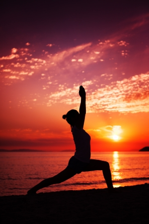 Woman Practicing Yoga at Sunset photo