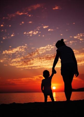 madre e hijo: Siluhettes de la madre y del hijo por el mar al atardecer Foto de archivo