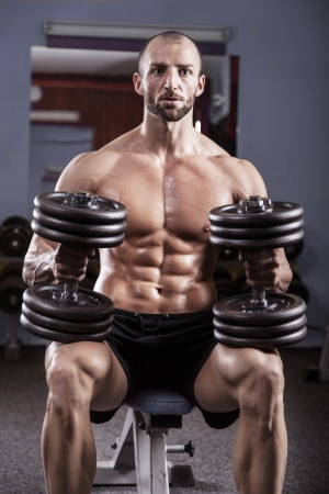 pectoral: Powerful muscular man lifting weights Stock Photo