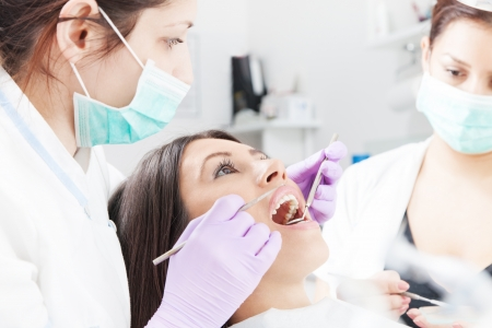 Woman having checkup at dental surgery photo