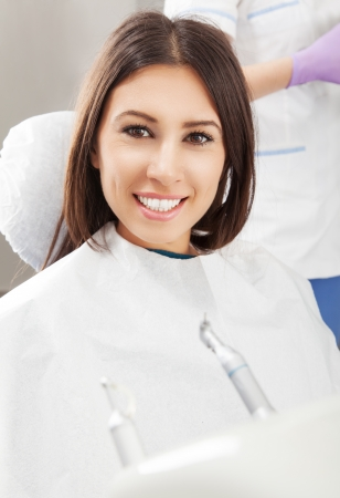 Happy young woman patient at the dentist smiling photo