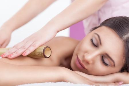 bambu: Mujer joven disfrutar de un masaje en el spa de bamb� de enfoque central selectivo, DOF