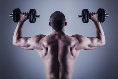 bodybuilder training: Rear view of bodybuilder training with dumbbells  Back muscles Stock Photo