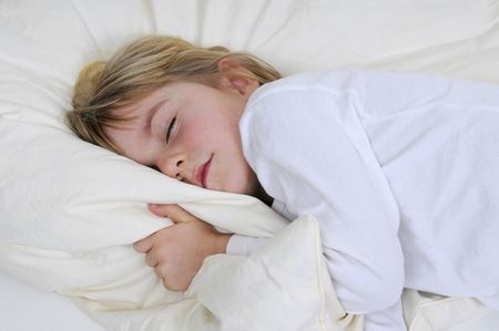 Blond little girl sleeps in bed