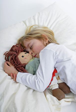 Blond little girl with puppet sleeps in bed