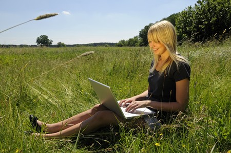 computer training: young woman with laptop on a meadow Stock Photo