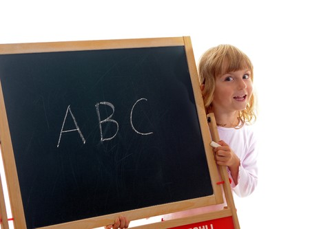 little girl behind a board with ABC Stock Photo