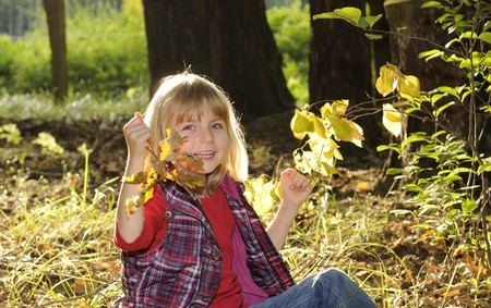 romp: little girl playing in the autumn forest Stock Photo