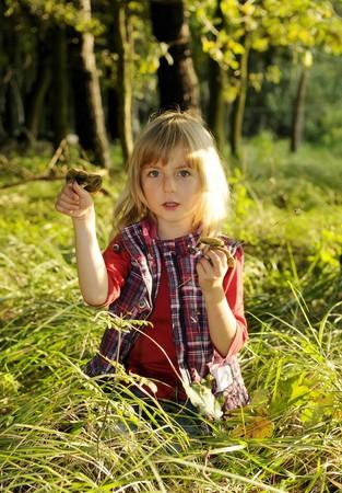 gathers: bambina raccoglie funghi nel bosco
