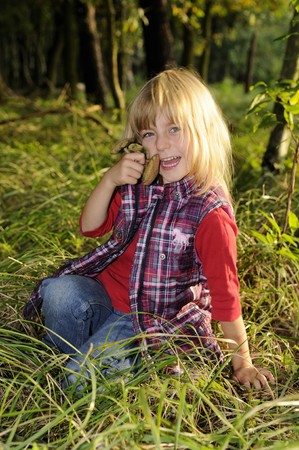 cull: little girl gathers mushrooms in the forest
