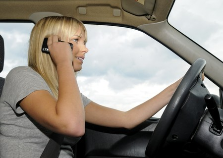 forbade: young woman with mobile phone in the car