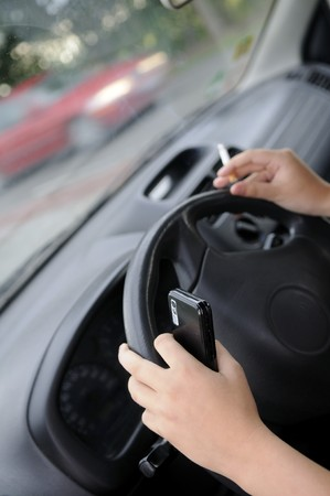 cigarette and mobile phone at the wheel Stock Photo - 7893719