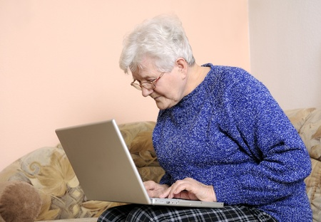 grizzled: older woman working on laptop Stock Photo