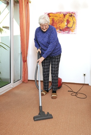 elderly woman with vacuum cleaner