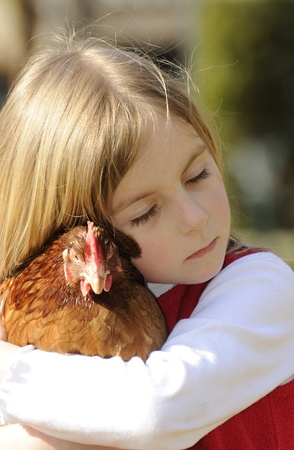 little girl hugging a chicken Stock Photo