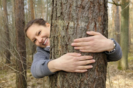 young woman hugging a tree