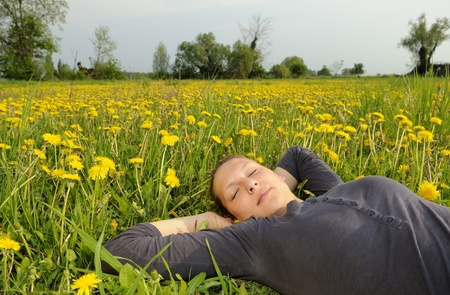 young woman lies on a flower meadow Stock Photo - 9519162