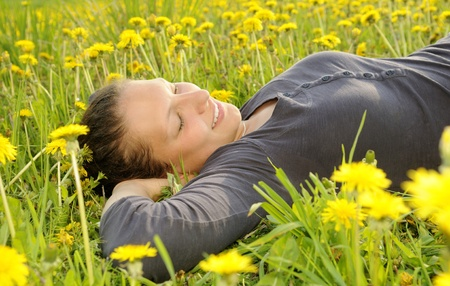 young woman lies on a flower meadow Stock Photo - 9519160