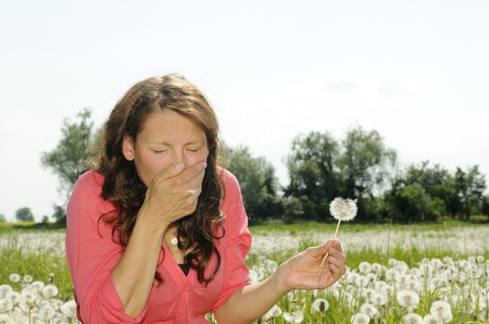 sniff: young woman sneezes on a flower meadow Stock Photo