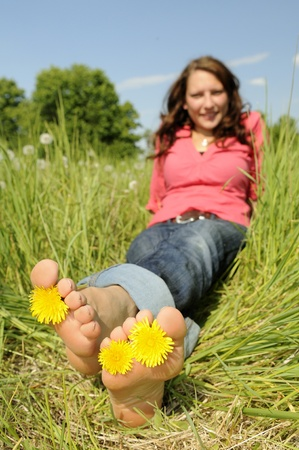 female soles: young woman is barefoot in a meadow