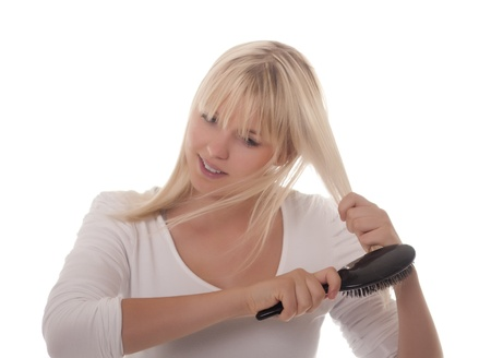 young blond woman combing her hair photo