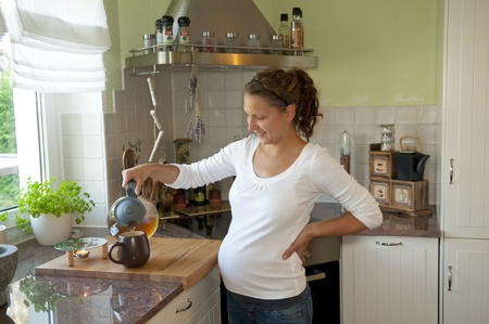 stand teapot: pregnant young woman pouring tea