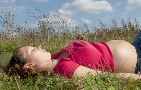 sleep well: pregnant young woman relaxing on a meadow