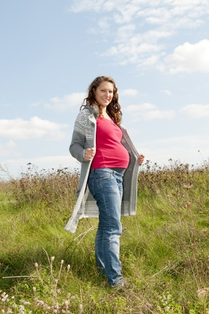 pregnant jeans: pregnant young woman on a meadow Stock Photo