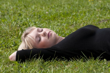 young woman lying on a meadow photo