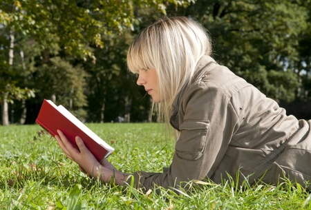 young woman reading a book on a meadow photo