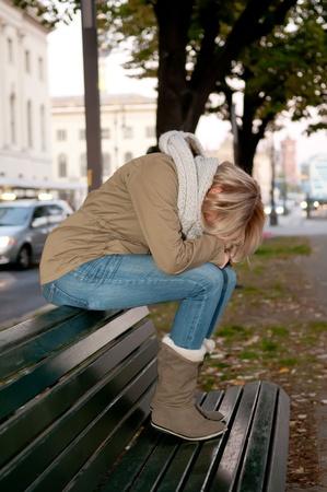 persona triste: joven triste sentado en un banco Foto de archivo