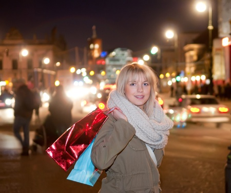 young woman with shopping bags in the city at night photo