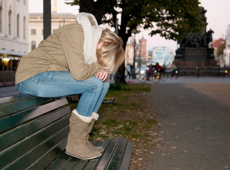 sad young woman sitting on a bench photo