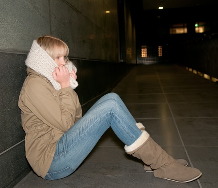 sad young woman sitting on the street Stock Photo
