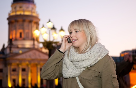joyfully: young woman phoned in the city at evening