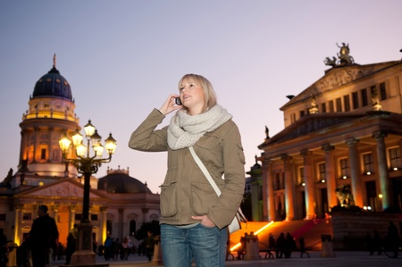 young woman phoned in the city at evening photo