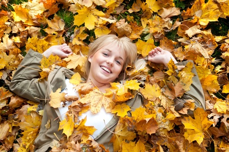 japanese fall foliage: young woman  lying in autumn leaves